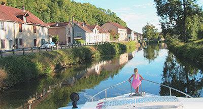 Mädchen sitzt am Bug eines Le Boat Hausbootes